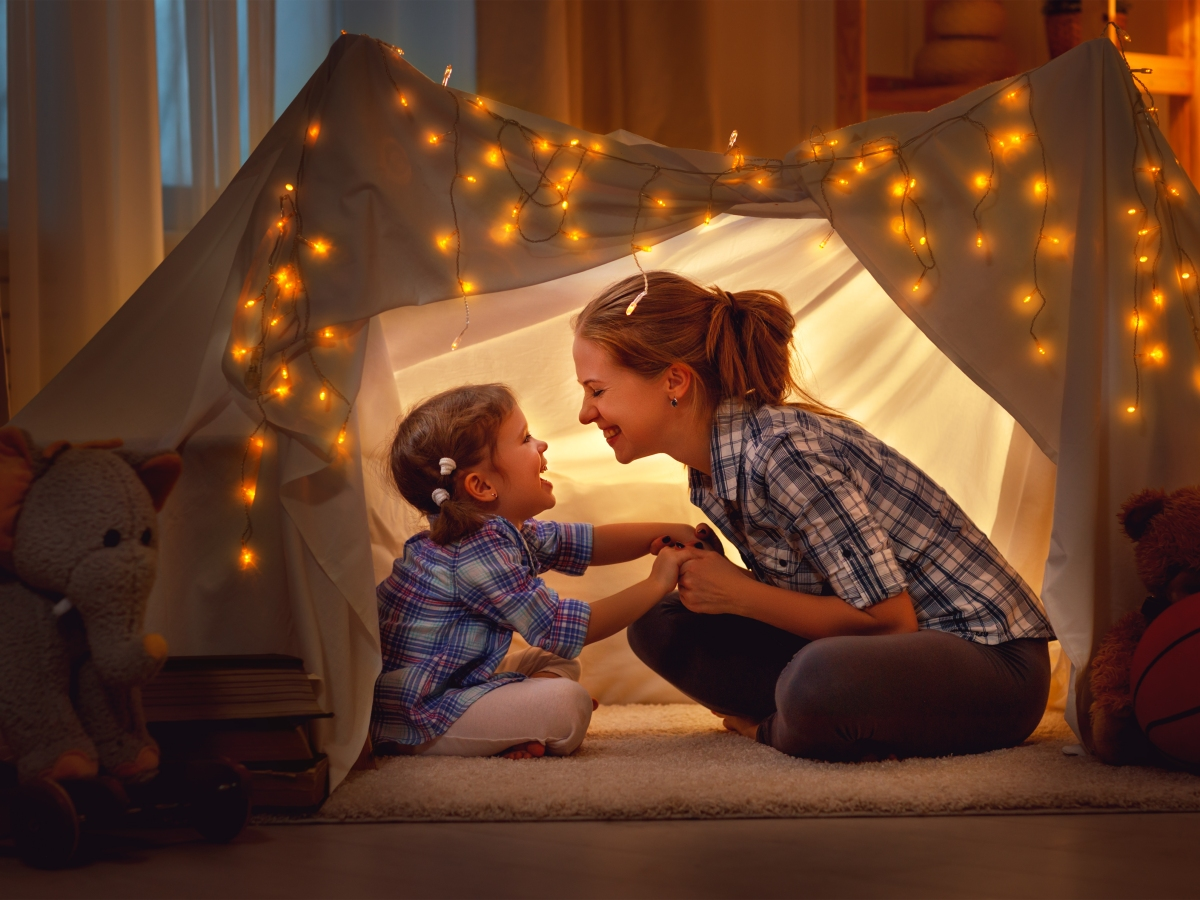 A mother and daughter laugh and enjoy each other in a tent made of sheets and twinkle lights